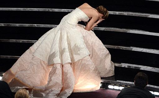 Jennifer Lawrence é traída pelo seu vestido e cai nos degraus para receber seu Oscar. (photo by popwatch.ew.com)