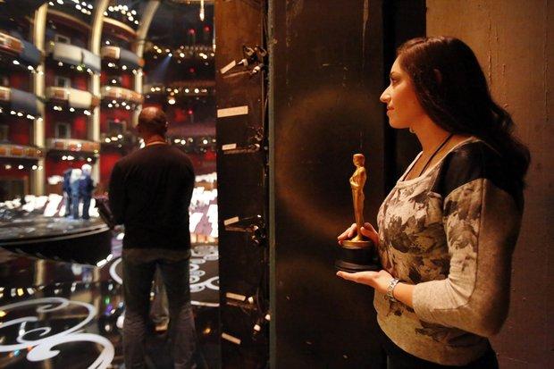 Uma dos seis estudantes de Cinema aguarda o anúncio do vencedor para entrar com a estatueta (photo by latimes.com)