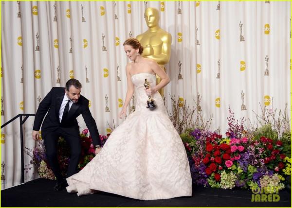 Jean Dujardin ajuda Jennifer Lawrence com o vestido que lhe causou um tombo na escada para o palco do Oscar (photo by justjared.com)