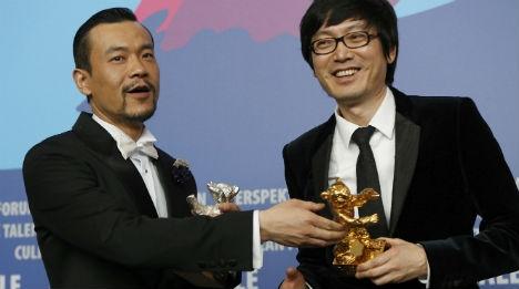 À esquerda, o ator Liao Fan ao lado do diretor Yi'nan Diao, vencedor do Urso de Ouro por Black Coal, Thin Ice (photo by www.thelocal.de)