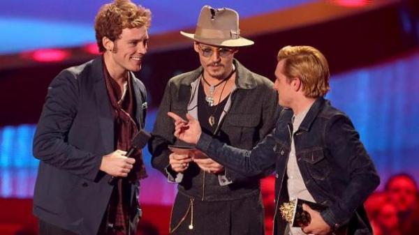 Os atores Sam Claflin (esq) e Josh Hutcherson (dir) recebem prêmio de Melhor Filme das mãos de Johnny Depp (centro). (photo by straitstimes.com)