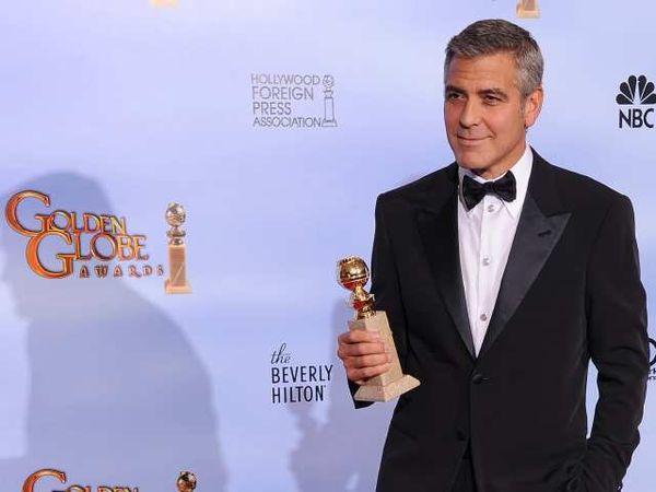 George Clooney com um de seus Globos de Ouro (photo by latimesblogs.latimes.com)