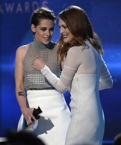 Julianne Moore recebe o prêmio de Atriz das mãos de Kristen Stewart, sua colega de trabalho no filme Still Alice. (photo by ibtimes.co.in)