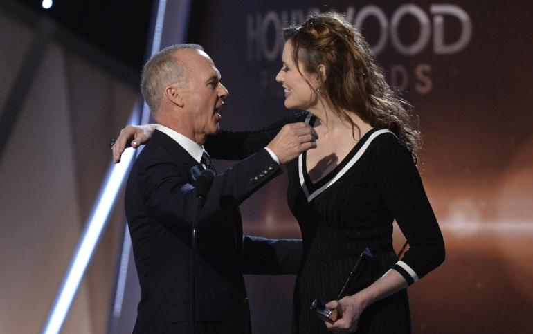 """Consolo nos braços de Geena Davis: Michael Keaton leva prêmio pelo conjunto da obra, e não por Homem-Pássaro, considerado seu grande """"comeback"""" (photo by ibtimes.com)"""