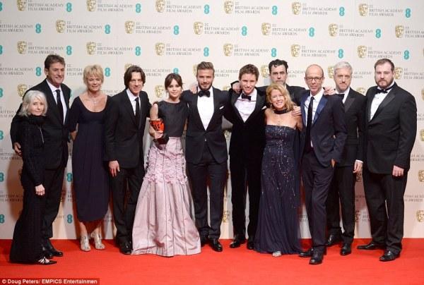 A equipe de A Teoria de Tudo posa com o prêmio de Melhor Filme Britânico. No centro, o diretor James Marsh, Felicity Jones, David Beckham (que entregou o prêmio) e Eddie Redmayne (photo by Doug Peters/EMPICS Entertainment)