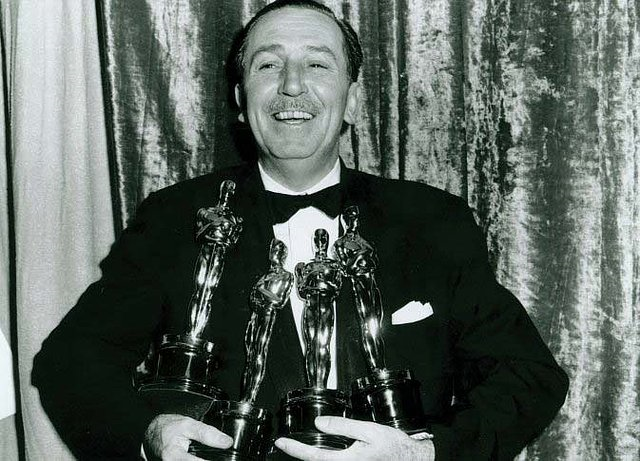 Walt Disney segura seus 4 Oscars vencidos na mesmo noite, um recorde jamais batido até hoje (photo by moviepilot.com)