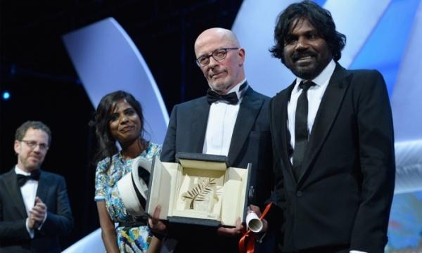 Jacques Audiard (centro) recebe a Palma de Ouro ao lado dos atores do filme Dheepan: Jesuthasan Antonythsan e Kalieaswari Srinivasan. Ao fundo, o presidente do júri, Ethan Coen (photo by theguardian.com)