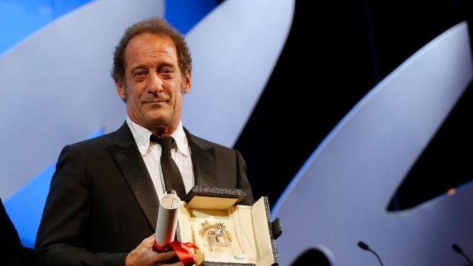 Vencedor do prêmio de interpretação masculina, o ator francês Vincent Lindon posa com o prêmio por The Measure of a Man (photo by news.yahoo.com)