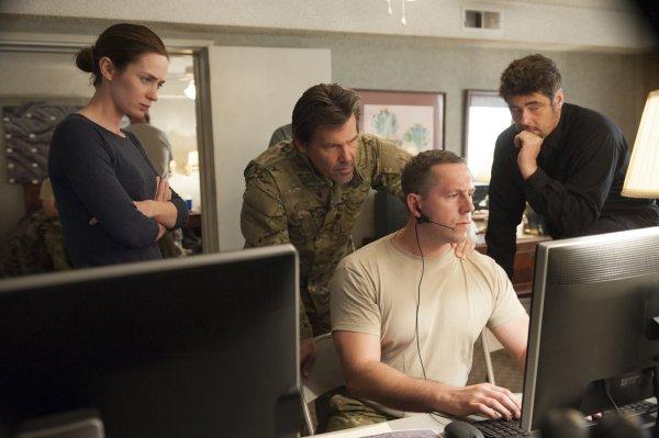 Em segundo plano, da esquerda para a direita: Emily Blunt, Josh Brolin e Benicio Del Toro em cena de Sicario: Terra de Ninguém (photo by cine.gr)