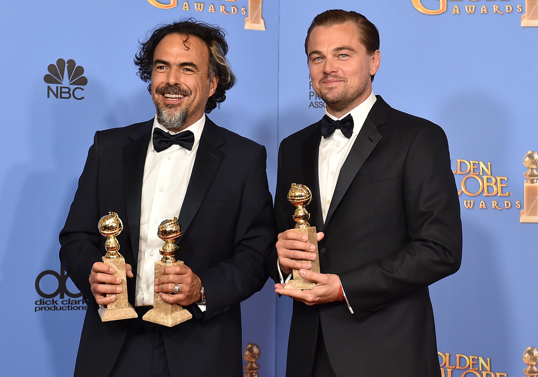 À esquerda, Alejandro González Iñárritu com duas estatuetas por Filme e Diretor, enquanto Leonardo Dicaprio com a de Melhor Ator por O Regresso (Photo by Jordan Strauss/Invision/AP - forbes.com)