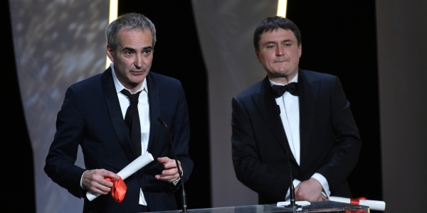 "Romanian director Cristian Mungiu (R) and French director Olivier Assayas talk on stage wafter being awarded with the Best Director prize, respectively for the film ""Graduation (Bacalaureat)"" and ""Personal Shopper"" during the closing ceremony of the 69th Cannes Film Festival in Cannes, southern France, on May 22, 2016. / AFP PHOTO / ALBERTO PIZZOLI"